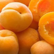 Pile of apricots, some whole, some cut in half.