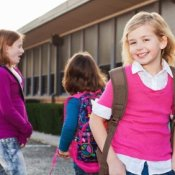 Three school age girls wearing backpacks.