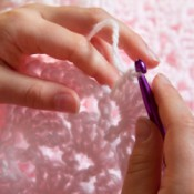 A person crocheting a pink baby blanket.