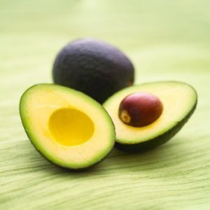 Two avocados, one cut in half with the seed inside.
