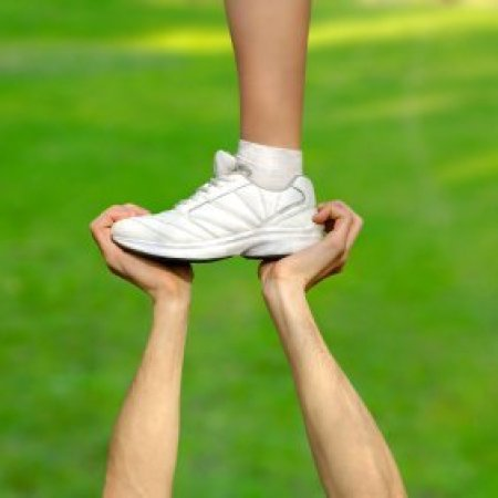 Upclose photo of a cheerleaders foot being held up by another person.