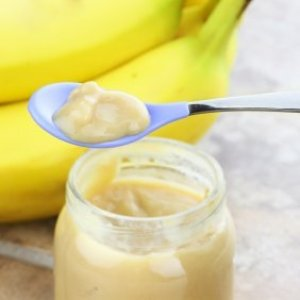 Jar of baby food with a spoon and bananas in the background.