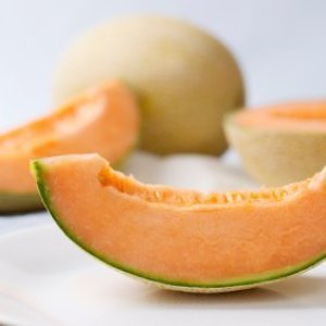 Slice of cantaloupe with other cantaloupes in the background.