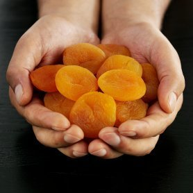 Someone holding a handful of dried apricots.