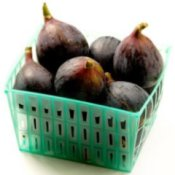 Green plastic basket of fresh figs.