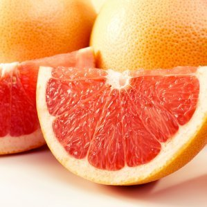 Grapfruit wedge with grapefruits in the background.