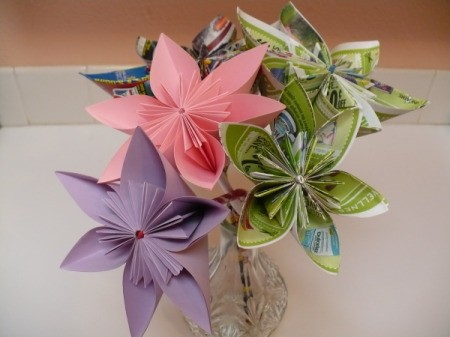 bouqet of paper flowers that includes a pink flower, a purple flower and 3 multi-colored flowers made from advertisements in a crystal vase
