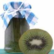 A jar of kiwifruit jam and half of a kiwi.