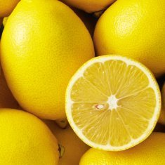 A half lemon sitting ontop of a pile of whole lemons.