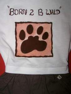 A baby's onsie with a fabric paint design of a paw and the words