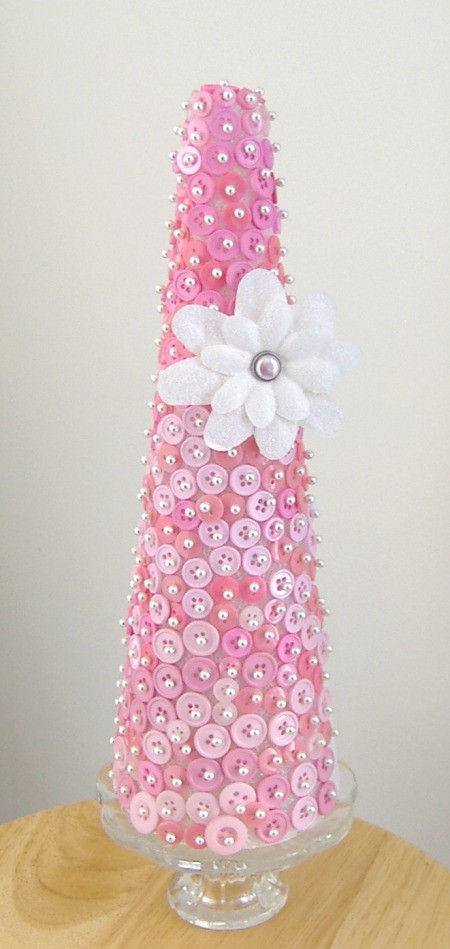 Styrofoam cone covered with pink buttons. The finished cone is sitting in a pedestal candy dish.