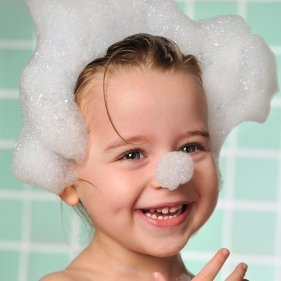 Toddler with bubbles on hair and end of nose.