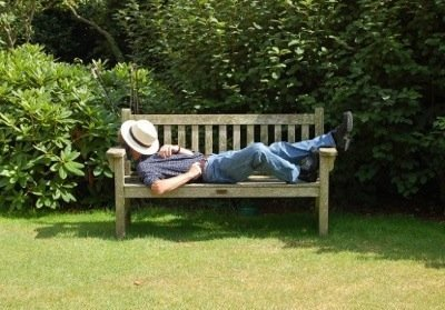 Man snoozing on garden bench