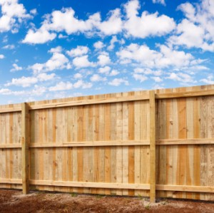Building a Fence, Six Foot Tall Cedar Fence with Blue Sky in the Background