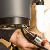 Repairing a Garbage Disposal (Disposer), Man's hands holding a power screwdriver to a garbage disposal.