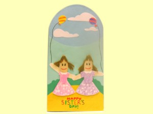 Finished sister card, two popsicle stick girls on a blue background with clouds
