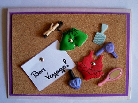 Finished Bon Voyage Card with foam swimsuits, brush, curling iron attached to cork board with brads.