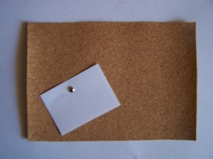 Cork Board wth Paper Note attached with a brad.