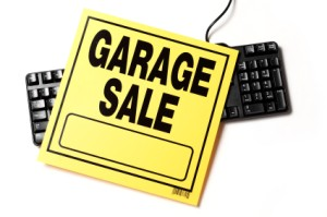 Garage Sale sign laying over top of a black keyboard