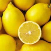 Half a lemon on a pile of whole lemons.