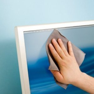 A person cleaning a flat screen monitor with a cloth.