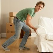 Young guy moving a white sofa