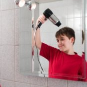 Cleaning Bathroom Mirrors, Reflection in a mirror of boy drying his hair with a blow dryer.