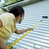 Cleaning Vinyl Siding, A woman scrubbing the siding of her house.
