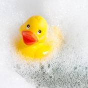 Rubber ducky floating in a bubble bath.