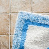 A blue and white rug on a tile floor.