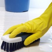 Gloved hand scrubbing a tile floor with a brush.