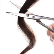 Scissors cutting a lock of dark hair.