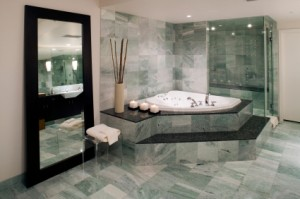 A marble spa tub and floor in a beautiful bathroom.