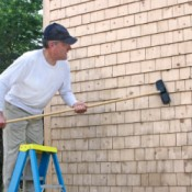 Man Cleaning Wood Siding