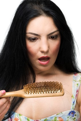 Woman Looking Shocked at the Hair in Her Brush