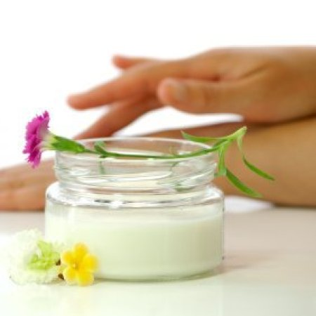 Jar of hand cream with flowers and woman's hands applying cream in the background.