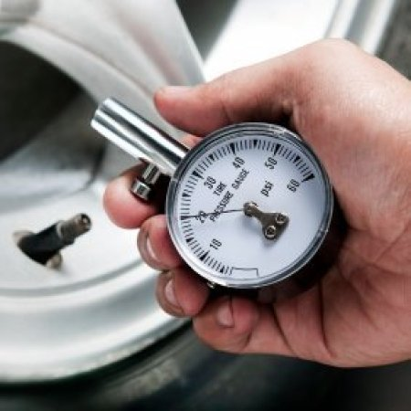 Checking Your Vehicle's Tire Pressure, Man holding a tire gauge, with tire in background.