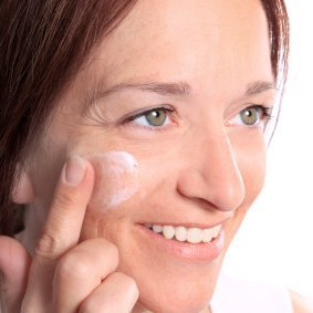 Woman applying wrinkle cream to her face.