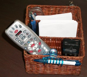 A basket with TV remotes, pens, paper and other small useful tools.