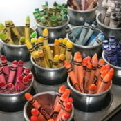 Crayons sorted by color inside small pots in muffin pan.