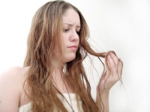 A woman looking at the ends of her damaged hair.