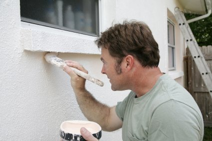 Photo of a man painting his house.