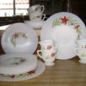 Tableware set: white with red flowers and leaf spray around half of outside edge. The edges appear to be ruffled.
