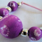 purple and white wooden batik beads strung with gold pony beads