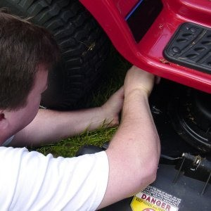Man tinkering with a riding mower.