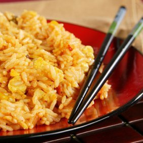 Plate of fried rice with chopsticks.