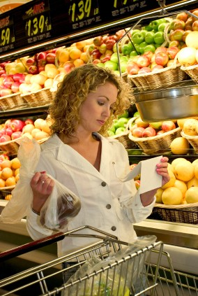 Woman Consulting Her Shopping List in the Supermarket