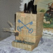 chick feeder covered in old paper with cut out of skeleton keys crossing each other, a few strands of raffia wrap the box near the bottom wiht a feather and a pewter and rhinestone button on it, the feeder is filled with pens
