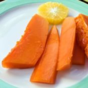Slices of peeled papaya on a plate with an orange slice.