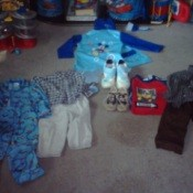 Used children's clothing items laid out on floor
